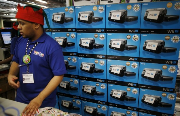 A cashier stands in front of a display of Nintendo Wii U gamepads and consoles in a Toys R Us store on Thanksgiving Day in Times Square